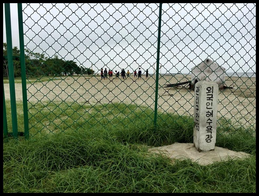 In Wonsan is ons een middag na 'n strand geneem, waar ons vir 'n uur of wat met ons tone in die sand kon speel. Daar was drade gespan aan weerskante van dié sowat 200m-lange strand. Ons deel van die strand was verlate, maar aan die ander kant van die onderskeie grensdrade waardeur ons ingehok is, kon ons talle Noord-Koreane sien waar hulle besig was om strandspeletjies te speel. Ek het grappenderw... See more
