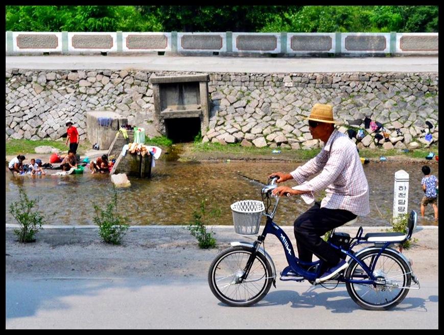 Ek het hierdie foto in Kaesong, 'n stad naby die grens met Suid-Korea, geneem. In die agtergrond kan vroue gesien word wat besig is om hulle wasgoed in 'n rivier te was.