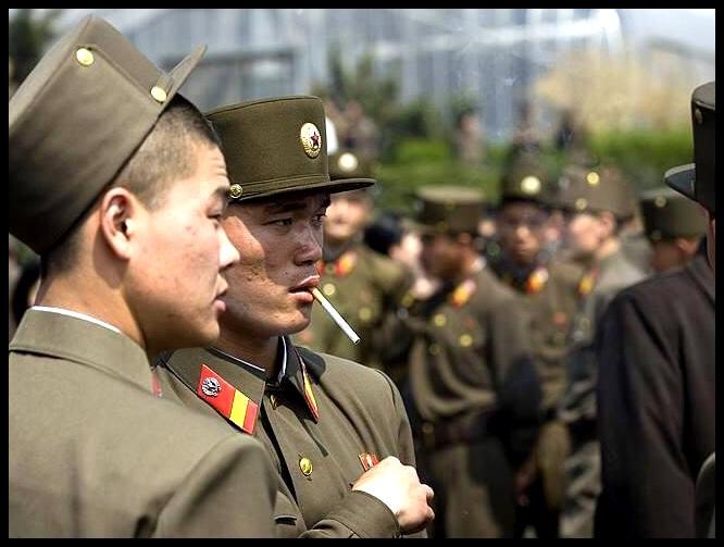 """Ons is streng verbied om enige foto's van enigiemand in 'n uniform te neem, en alhoewel ek hier en daar probeer het om ongesiens dié reël te omseil, het ek grootliks daarby gehou. 'n Franse fotograaf, Eric Lafforgue, was egter brawer as ek, en nadat hy die """"ongewensde"""" foto's wat hy in Noord-Korea geneem het gepubliseer het, is hy lewenslank uit dié land verban. Die volgende paar foto's is deur Lafforgue geneem, en ek leen dit dus net by hom. Dankie Eric! Hiérdie foto het die regime rooi laat sien, omdat dit soldate in ontspanne luim uitbeeld. Soldate is immers nie gewone mense met gewone behoeftes nie..."""