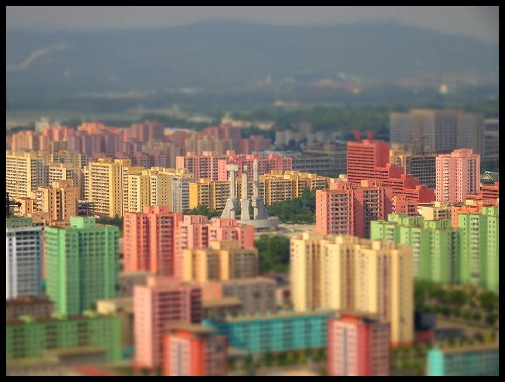 Die uitsig vanaf die Juche-toring oor Pyongyang. Die kleurvolle geboue is straks die enigste titsel kleur wat die inwoners van dié stad in hulle daaglikse bestaan beleef.  In die middel van dié foto kan die monument wat ter herdenking van die Koreaanse Werkersparty se stigting opgerig is, gesien word.