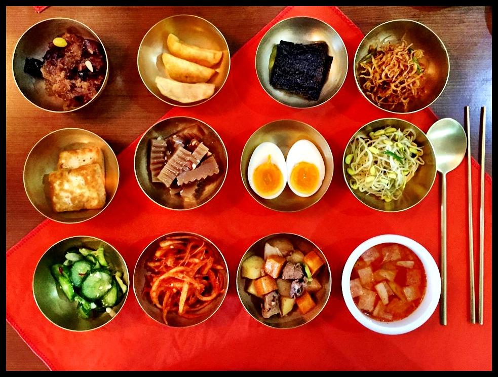 'n Tradisionele Koreaanse maaltyd. Van bo na onder, van links na regs: rys-en-pruimedantgereg, gebakte aartappelskywe, seegras, gerasperde soutvis, tofu, 'n gekookte eier, weet nie, gepekelde komkommer, weet nie, beesbredie, kimchee.