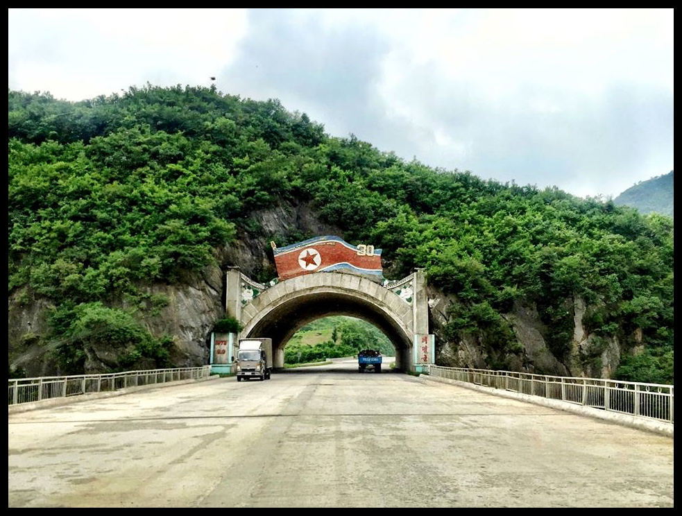 """'n Keurig versierde tonnel tussen Pyongyang en Wonsan. Let op die gehawende toestand van die """"snelweg""""."""