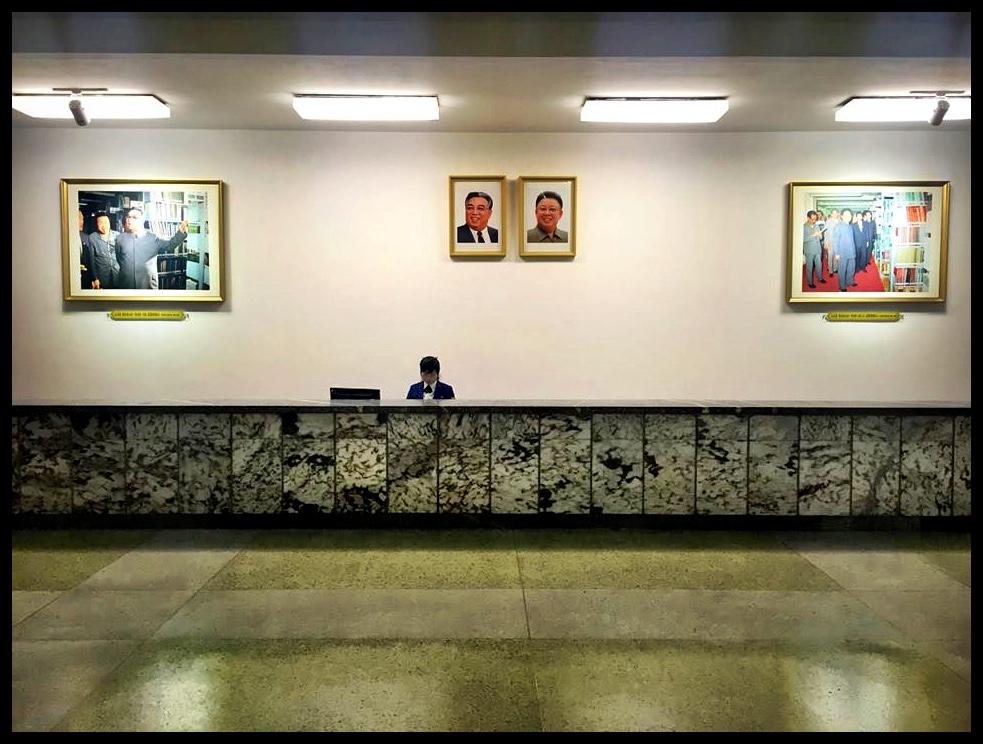 """Een van die bibliotekaresses van die """"Grand People's Study House"""" in Pyongyang. Volgens ons gids word 'n volle 30 miljoen boeke van reg oor die wêreld in dié biblioteek gehuisves. Ons kon egter nie ons oë daarop lê nie, aangesien dit, soos wat die gebruik mos oral in die wêreld is, in stoorkamers geberg word om dit teen """"ligskade"""" te beskerm. Langs dié dame was daar egter 'n gat in die muur wat met 'n vervoerband aan dié reuse-stoorkamers verbind is. Terwyl ons daar rondgestaan het, het twee Engelse boeke hulle verskyning op die vervoerband gemaak: """"Exotic Gardening"""" deur ene Ian Cooke, en """"The World of Sharks"""" deur Wendy Pfeffer. Ek betwyfel dit sterk of enige van dié twee outeurs al ooit naby daaraan was om vir die Nobelprys vir Literatuur te kwalifiseer, en daarom het ek ewe vroom gevra of sy dalk kan kyk of twee van my gunsteling-boeke dalk onder die 30 miljoen in hulle opgawelys tel. My entoesiasme vir George Orwell word egter nie deur die regime gedeel nie, want die behulpsame bibliotekaresse kon nie """"Animal Farm"""" óf """"1984"""" op haar stelsel vind nie. Surprise, surprise."""